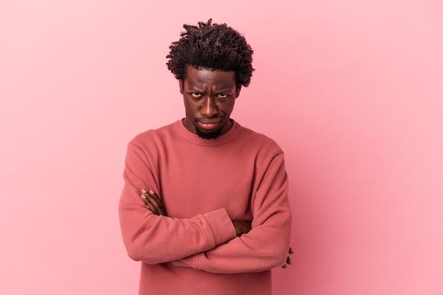 Jeune homme afro-américain isolé sur fond rose malheureux à la recherche à huis clos avec une expression sarcastique.