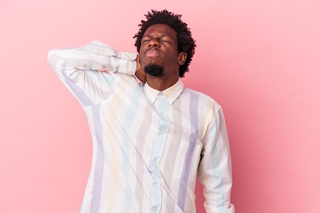 Jeune homme afro-américain isolé sur fond rose, massant le coude, souffrant après un mauvais mouvement.