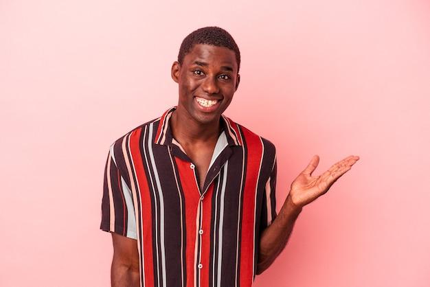 Jeune homme afro-américain isolé sur fond rose montrant un espace de copie sur une paume et tenant une autre main sur la taille.