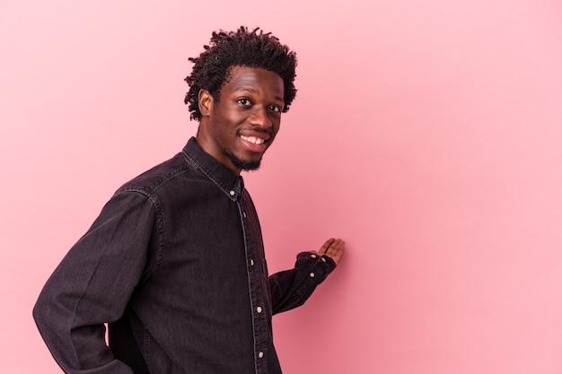 Jeune homme afro-américain isolé sur fond rose montrant une expression de bienvenue.