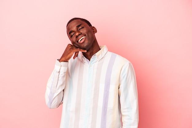 Jeune homme afro-américain isolé sur fond rose montrant un geste d'appel de téléphone portable avec les doigts.