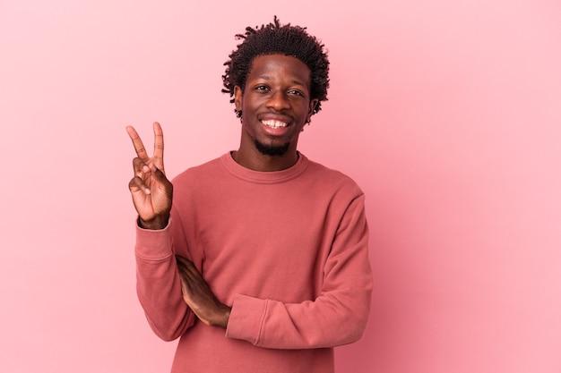 Jeune homme afro-américain isolé sur fond rose montrant le numéro deux avec les doigts.