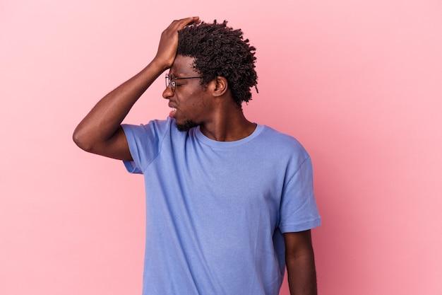Jeune homme afro-américain isolé sur fond rose oubliant quelque chose, frappant le front avec la paume et fermant les yeux.