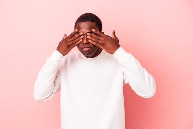 Jeune homme afro-américain isolé sur fond rose peur couvrant les yeux avec les mains.