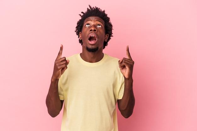 Jeune homme afro-américain isolé sur fond rose pointant vers le haut avec la bouche ouverte.