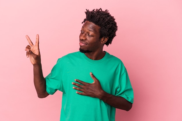 Jeune homme afro-américain isolé sur fond rose prêtant serment, mettant la main sur la poitrine.