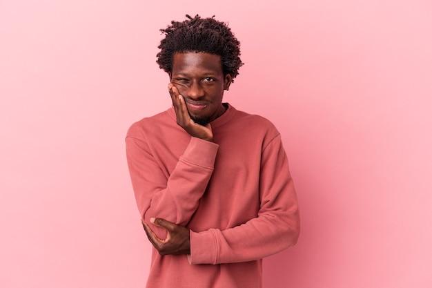 Jeune homme afro-américain isolé sur fond rose qui s'ennuie, est fatigué et a besoin d'une journée de détente.