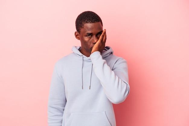 Jeune homme afro-américain isolé sur fond rose qui se sent triste et pensif, regardant l'espace de copie.