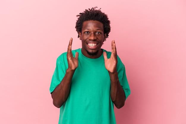 Jeune homme afro-américain isolé sur fond rose rit fort en gardant la main sur la poitrine.