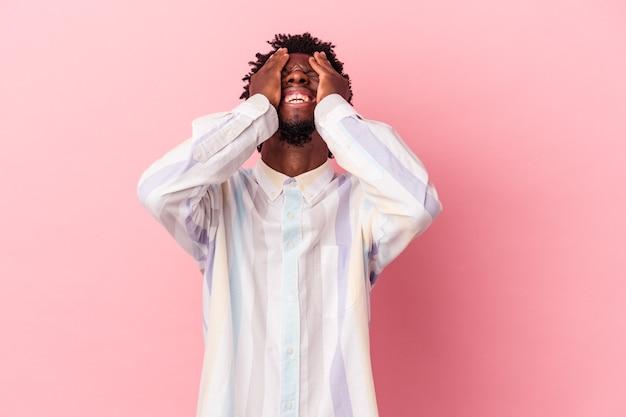 Jeune homme afro-américain isolé sur fond rose rit joyeusement en gardant les mains sur la tête. notion de bonheur.