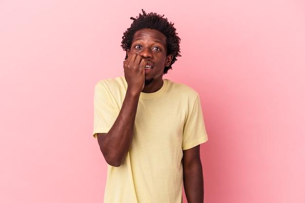 Jeune homme afro-américain isolé sur fond rose se rongeant les ongles, nerveux et très anxieux.