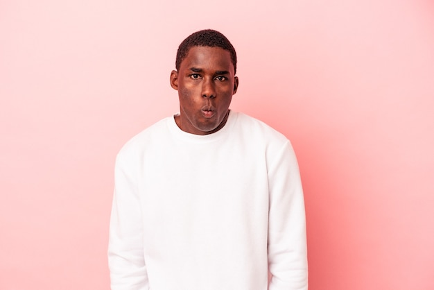 Jeune homme afro-américain isolé sur fond rose souffle les joues, a une expression fatiguée. concept d'expression faciale.