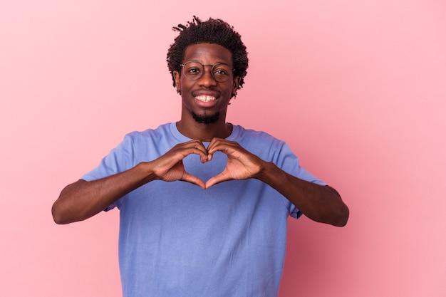 Jeune homme afro-américain isolé sur fond rose souriant et montrant une forme de coeur avec les mains.