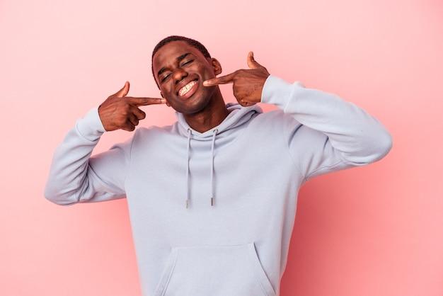 Jeune homme afro-américain isolé sur fond rose sourit, pointant du doigt la bouche.