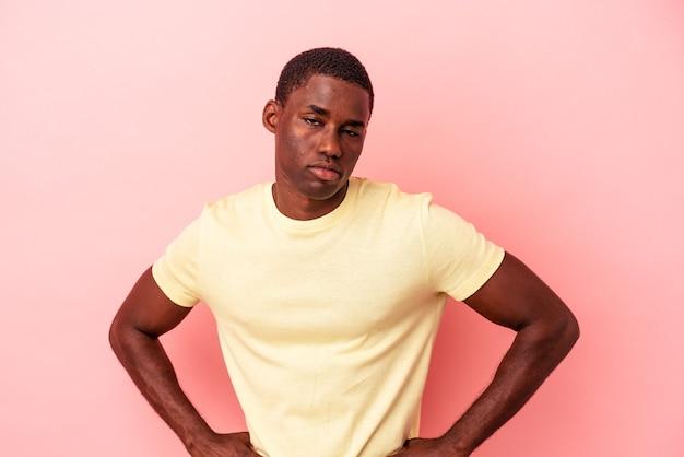 Jeune homme afro-américain isolé sur fond rose, visage triste et sérieux, se sentant misérable et mécontent.