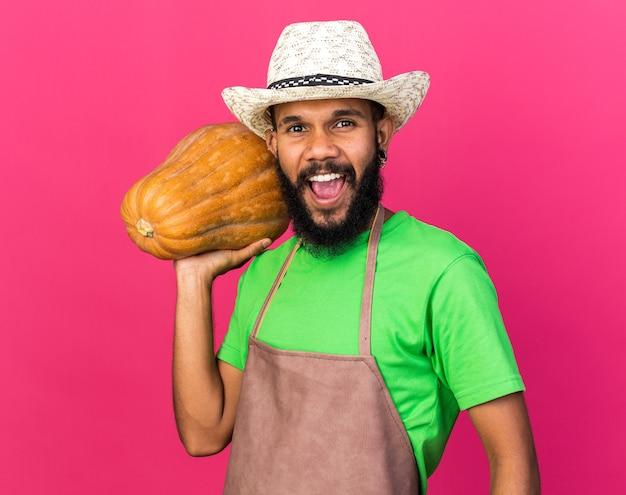 Jeune homme afro-américain de jardinier excité portant un chapeau de jardinage tenant une citrouille sur l'épaule