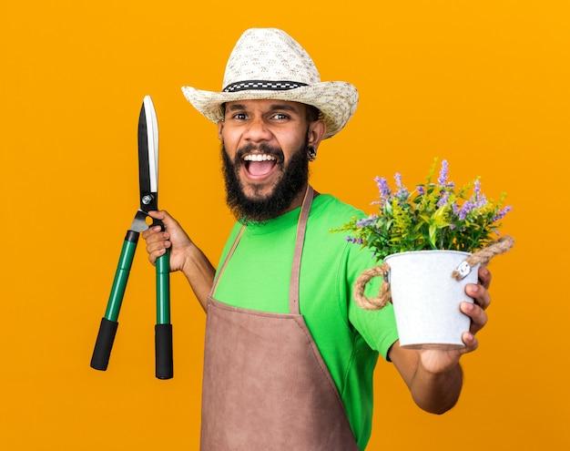 Jeune homme afro-américain jardinier excité portant un chapeau de jardinage tenant une tondeuse et une fleur dans un pot de fleurs isolé sur un mur orange