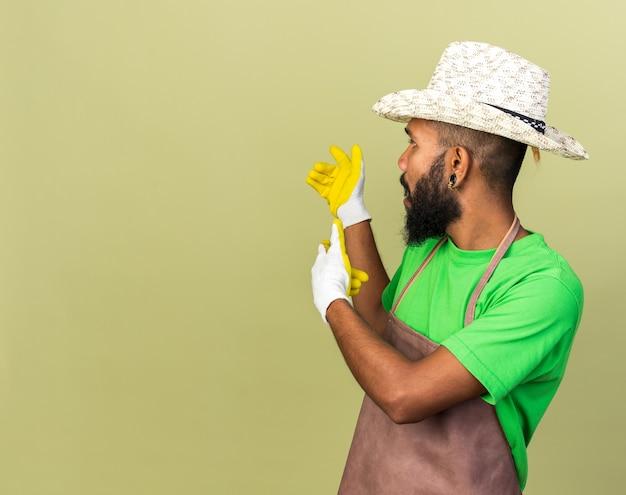 Jeune homme afro-américain jardinier portant un chapeau de jardinage avec des gants pointe derrière