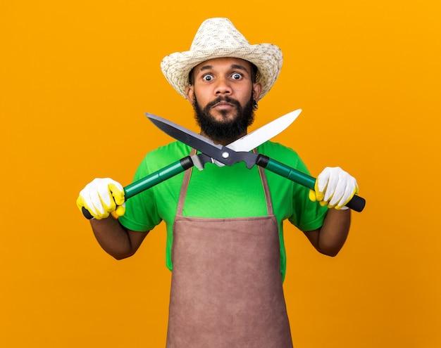 Jeune homme afro-américain de jardinier surpris portant un chapeau de jardinage et des gants tenant des tondeuses isolées sur un mur orange