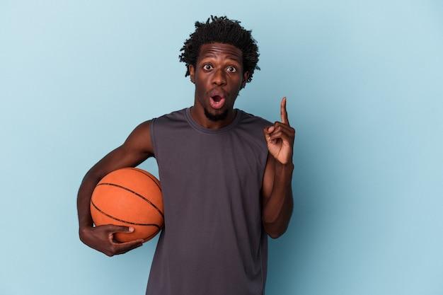 Jeune homme afro-américain jouant au basket-ball isolé sur fond bleu ayant une idée, concept d'inspiration.