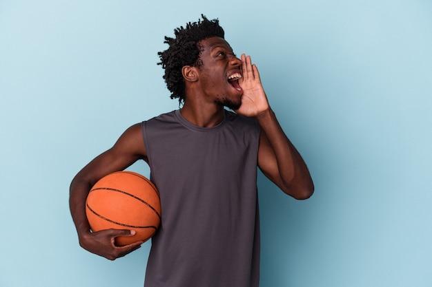 Jeune homme afro-américain jouant au basket-ball isolé sur fond bleu criant et tenant la paume près de la bouche ouverte.