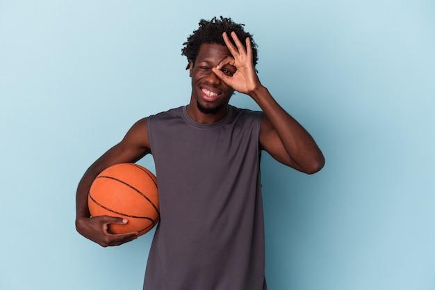 Jeune homme afro-américain jouant au basket-ball isolé sur fond bleu excité en gardant un geste ok sur les yeux.