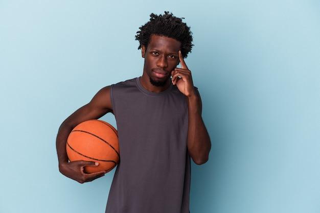 Jeune homme afro-américain jouant au basket-ball isolé sur fond bleu pointant le temple avec le doigt, pensant, concentré sur une tâche.