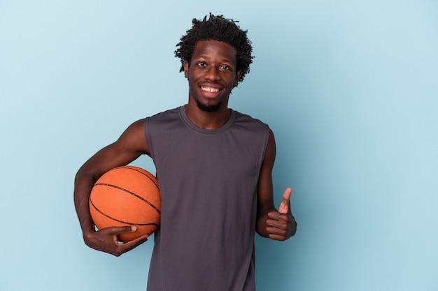 Jeune homme afro-américain jouant au basket-ball isolé sur fond bleu souriant et levant le pouce vers le haut