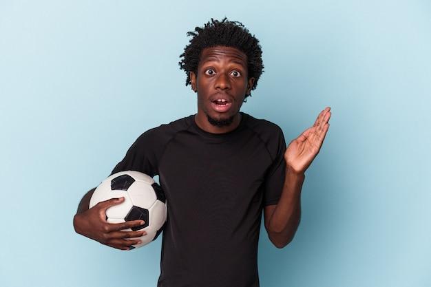 Jeune homme afro-américain jouant au football isolé sur fond bleu surpris et choqué.