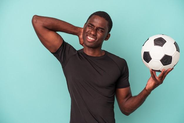 Jeune homme afro-américain jouant au football isolé sur fond bleu touchant l'arrière de la tête, pensant et faisant un choix.