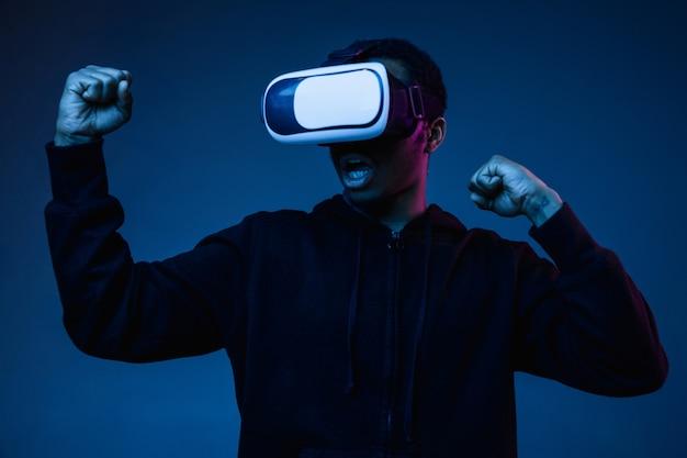 Jeune homme afro-américain jouant dans des lunettes vr en néon sur fond dégradé. portrait masculin