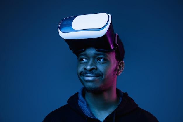Jeune homme afro-américain jouant dans des lunettes vr en néon sur gradient