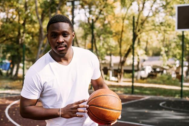 Un jeune homme afro-américain joue au basket-ball sur un terrain extérieur, souriant et regardant la caméra. sports de plein air.