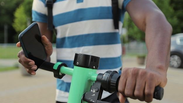 Un jeune homme afro-américain loue un scooter électrique à l'aide d'une application pour téléphone portable. l'homme a déverrouillé le scooter électrique avec son smartphone en gros plan