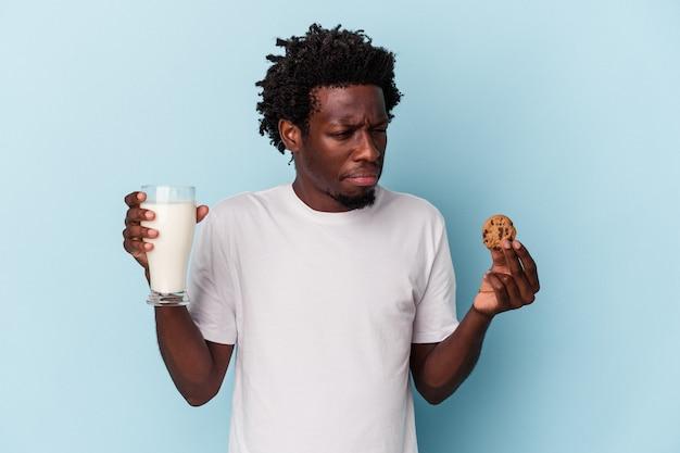 Jeune homme afro-américain mangeant des biscuits aux pépites de chocolat et buvant du lait sur bleu