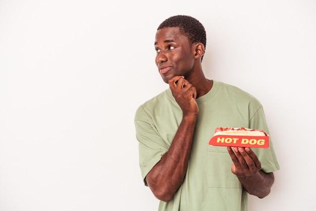 Jeune homme afro-américain mangeant un hot-dog isolé sur fond blanc regardant de côté avec une expression douteuse et sceptique.