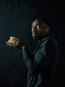 Le jeune homme afro-américain de manger un hamburger et à la recherche de suite sur fond de studio noir