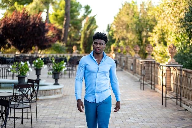 Jeune homme afro-américain marchant sur la terrasse d'un bar.