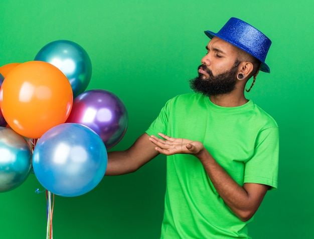 Un jeune homme afro-américain mécontent portant un chapeau de fête tenant et pointant des ballons isolés sur un mur vert