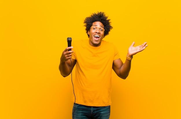Jeune homme afro-américain avec un microphone chantant contre ou