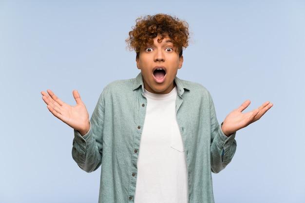 Jeune homme afro-américain sur un mur bleu isolé avec une expression faciale choquée