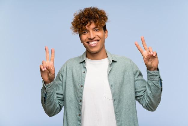 Jeune homme afro-américain sur mur bleu isolé montrant le signe de la victoire à deux mains