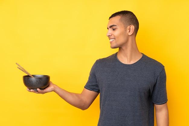 Jeune homme afro-américain sur mur jaune isolé avec une expression heureuse tout en tenant un bol de nouilles avec des baguettes