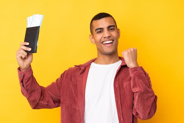 Jeune homme afro-américain sur mur jaune isolé heureux en vacances avec passeport et billets d'avion