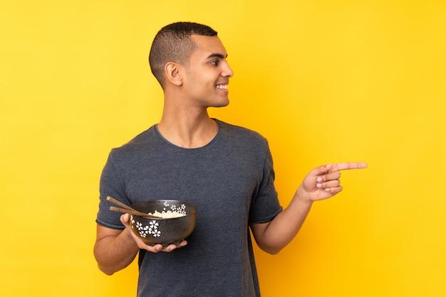 Jeune homme afro-américain sur mur jaune isolé pointant vers le côté pour présenter un produit tout en tenant un bol de nouilles avec des baguettes