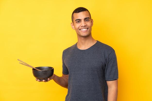 Jeune homme afro-américain sur mur jaune isolé souriant beaucoup tout en tenant un bol de nouilles avec des baguettes