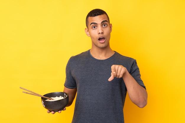 Jeune homme afro-américain sur mur jaune isolé surpris et pointant vers l'avant tout en tenant un bol de nouilles avec des baguettes