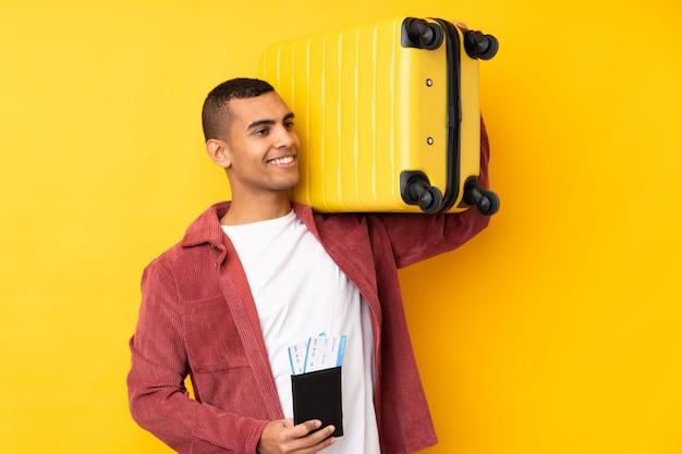 Jeune homme afro-américain sur mur jaune isolé en vacances avec valise et passeport