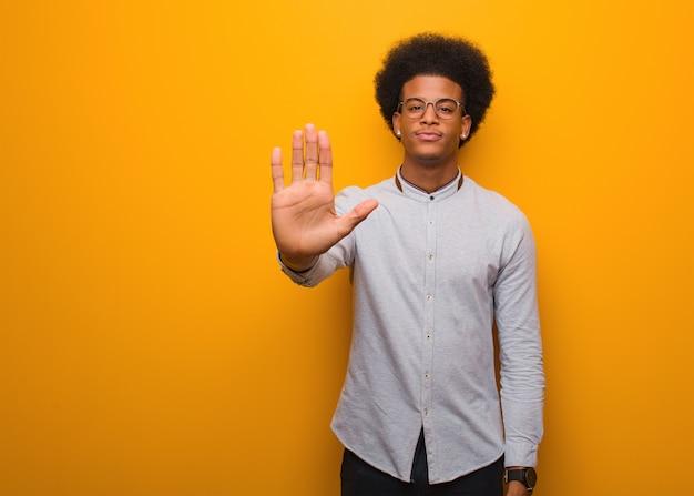 Jeune homme afro-américain sur un mur orange, mettant la main devant