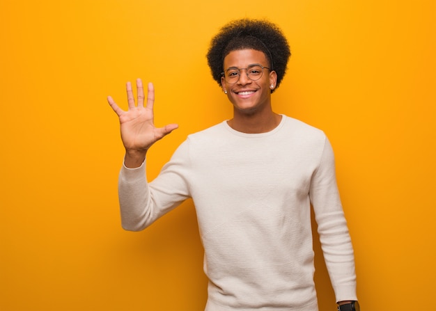 Jeune homme afro-américain sur un mur orange montrant le numéro cinq